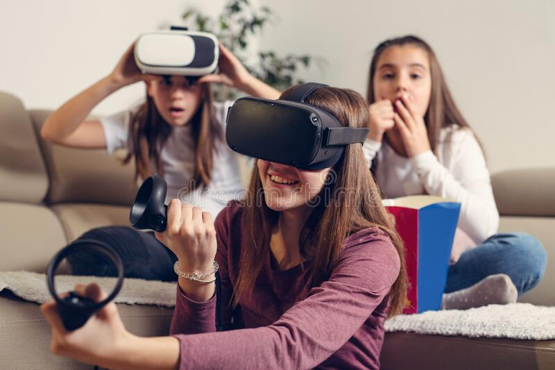 Friends playing video games wearing virtual reality glasses royalty free stock image