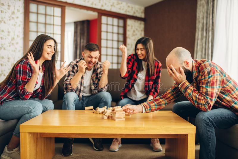 Friends plays jenga at home, the tower has fallen. Board game requiring high concentration, entertainment for funny company royalty free stock photo