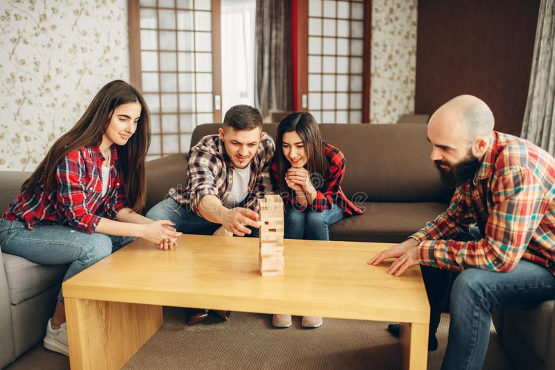 Friends plays jenga, man pulls block from tower. Friends plays table game at home, the men pulls wooden block from the tower. Board game requiring high royalty free stock photography