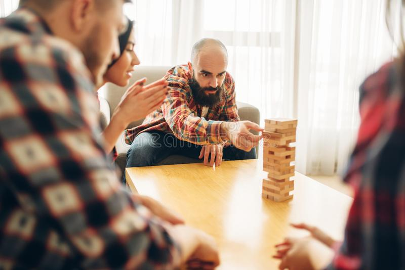 Friends plays jenga, man pulls block from tower. Friends plays table game at home, the men pulls wooden block from the tower. Board game requiring high royalty free stock photos