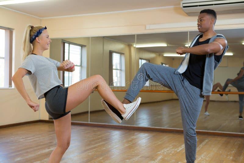Friends practicing dance against mirror on floor. Friends practicing dance against mirror on wooden floor at studio stock image