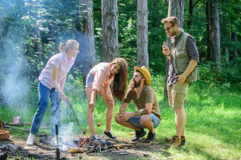 Friends prepare roasted sausages snacks nature background. Camping traditional meal prepared on fire with smoky aroma. Take a break to have snack. Company royalty free stock photos