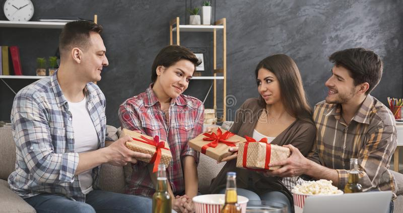 Friends presenting gifts to a girl celebrating her birthday. Happy friends presenting gifts to shy girl celebrating her birthday at home party stock image