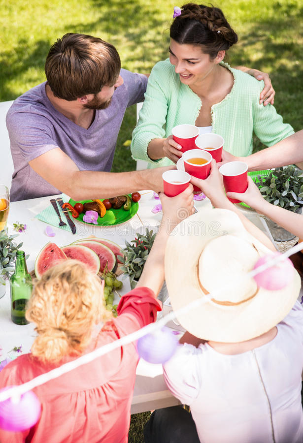 Friends proposing a toast. During garden party stock photo