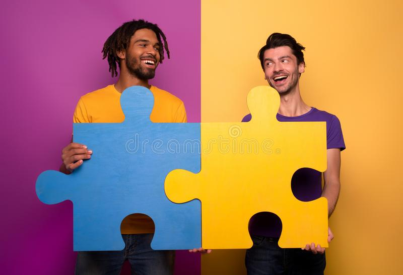 Friends with puzzles in hand over yellow background. Concept of integration, union and partnership. Happy Friends with puzzles in hand over yellow background stock image