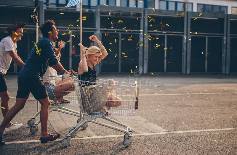 Friends racing with shopping cart. Multiethnic young people racing with shopping cart and blowing confetti. Young friends having fun on shopping carts royalty free stock images