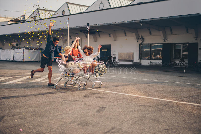 Friends racing with shopping carts on road. Young friends having fun on shopping trolleys and blowing confetti. Multiethnic young people racing with shopping royalty free stock photos