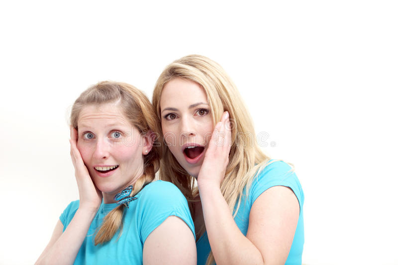 Friends reacting in astonishment. Two wide eyed female friends reacting in astonishment and incredulity as they stand close together with their hands to their stock photography