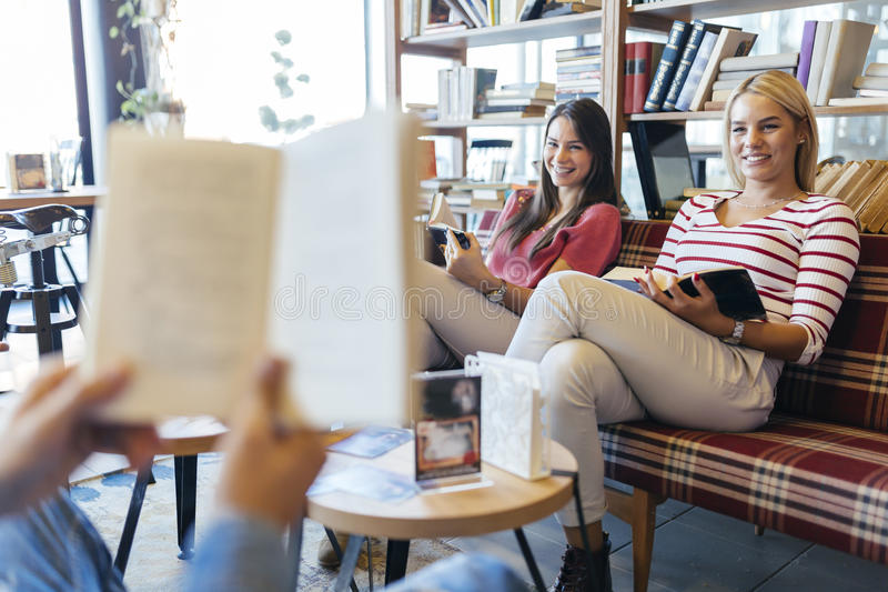 Friends reading books. And studying for exam together stock photography