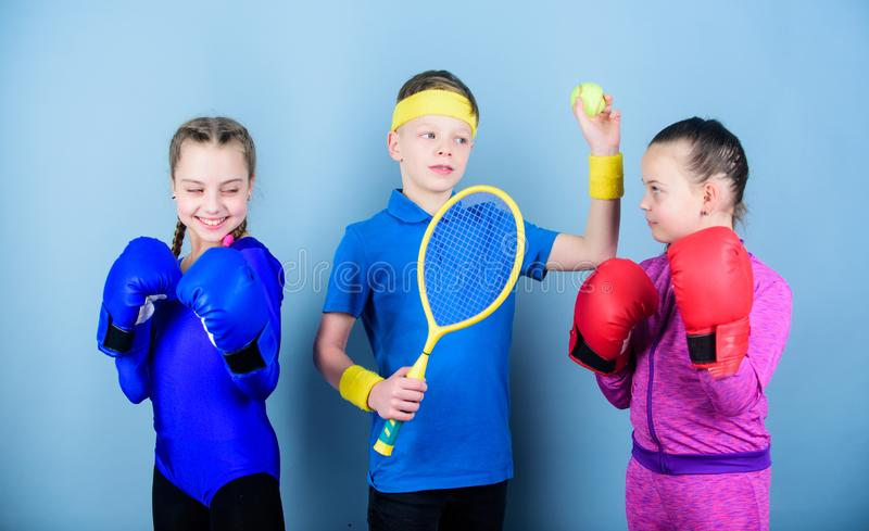 Friends ready for sport training. Sporty siblings. Child might excel completely different sport. Girls kids with boxing. Sport equipment and boy tennis player royalty free stock photo