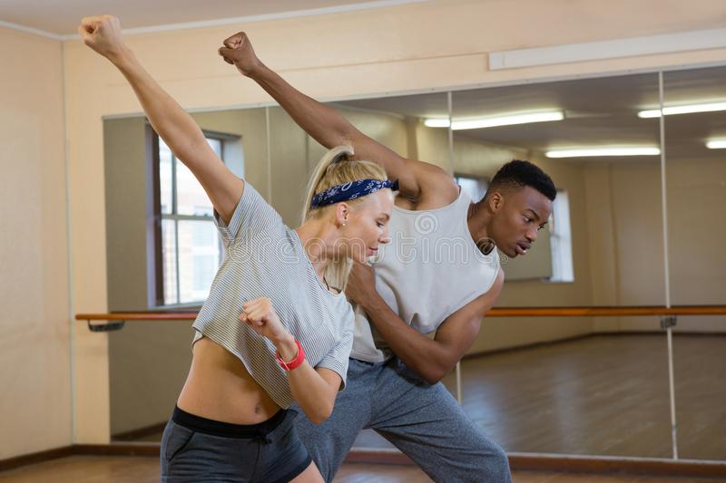 Friends rehearsing dance against mirror. Against mirror at studio royalty free stock photography