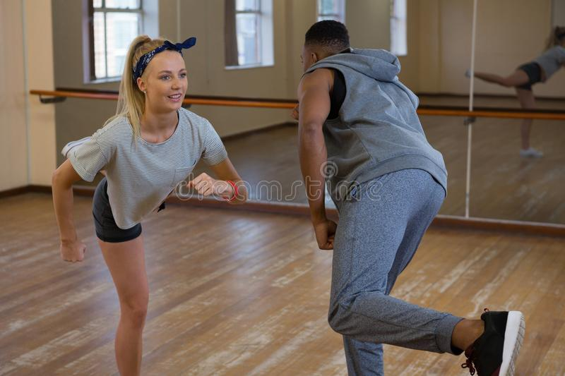Friends rehearsing dance against mirror on floor. Friends rehearsing dance against mirror on wooden floor at studio royalty free stock photos