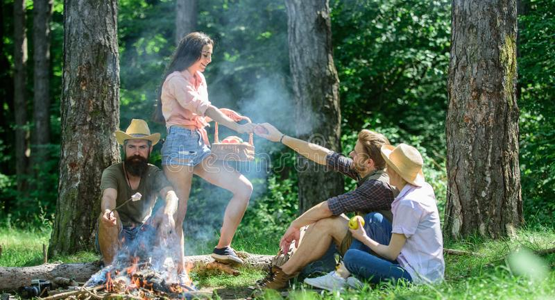 Friends relaxing near bonfire. Friends enjoy picnic eat food nature forest background. Plan for perfect day hike picnic. Pleasant hike picnic in forest stock image