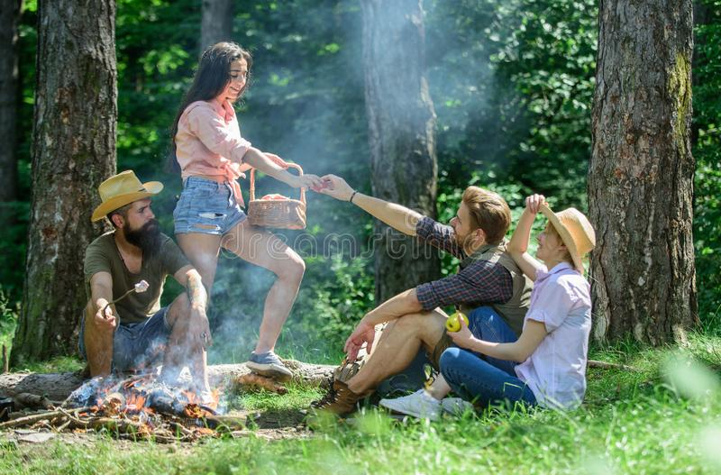 Friends relaxing near bonfire. Friends enjoy picnic eat food nature forest background. Plan for perfect day hike picnic. Company friends or family relaxing royalty free stock photo