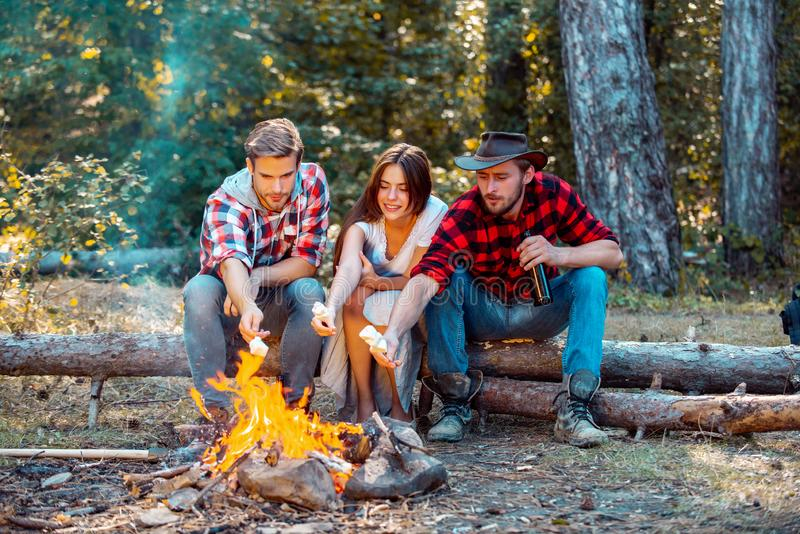 Friends relaxing near campfire after day hiking or gathering mushrooms. Friends enjoy weekend camp in forest. Enjoying royalty free stock photography