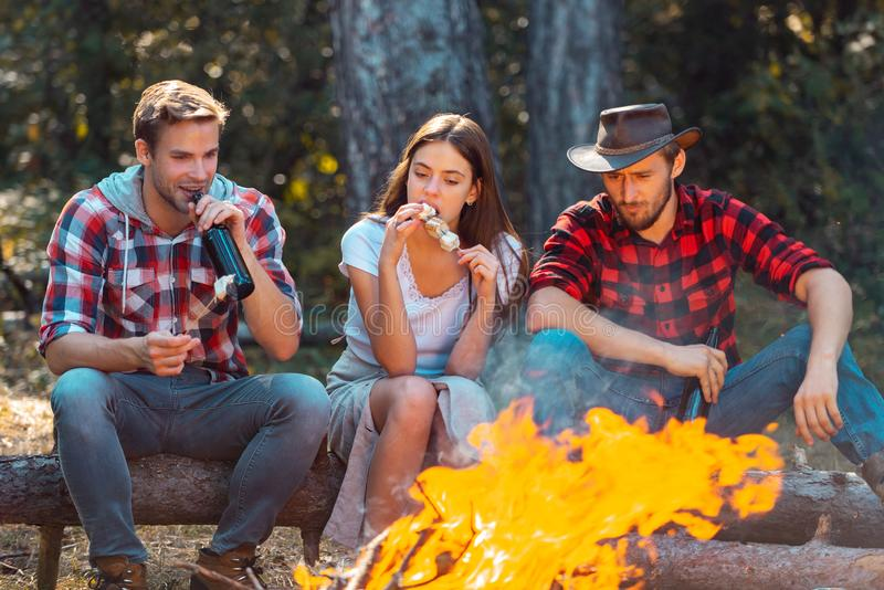 Friends relaxing near campfire after day hiking or gathering mushrooms. Tourism concept. Best friends spend leisure stock image