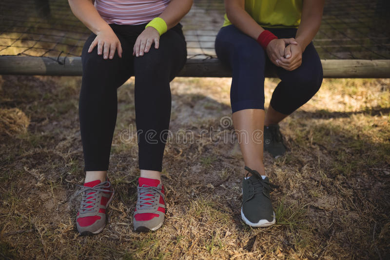 Friends relaxing on outdoor equipment during obstacle course royalty free stock photo