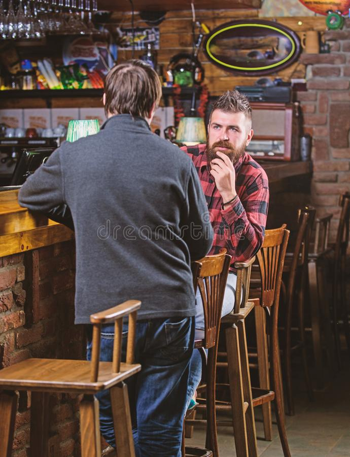 Friends relaxing in pub. Friendly conversation with stranger. Hipster brutal bearded man spend leisure with friend bar. Friends relaxing in pub. Friendly royalty free stock image