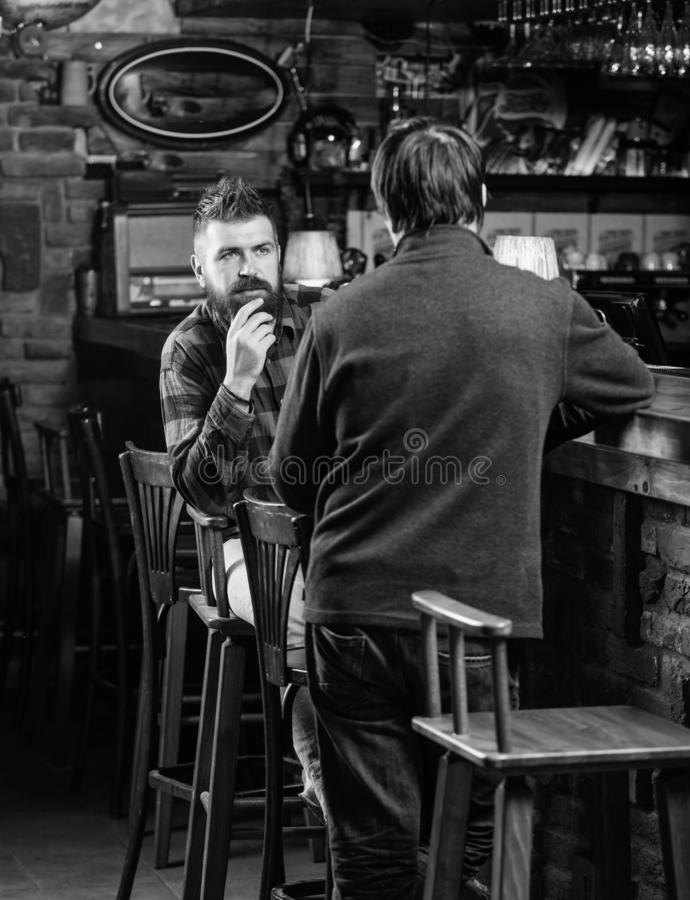 Friends relaxing in pub. Friendly conversation with stranger. Hipster brutal bearded man spend leisure with friend bar. Friends relaxing in pub. Friendly stock photo