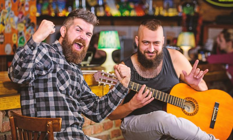 Friends relaxing in pub. Live music concert. Man play guitar in pub. Acoustic performance in pub. Hipster brutal bearded. With friend in pub royalty free stock photos