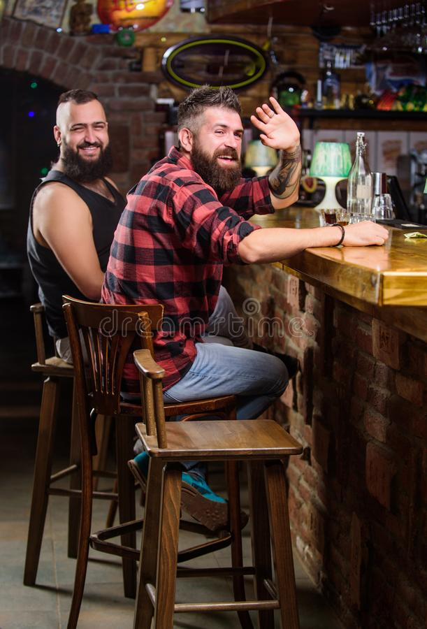 Friends relaxing in pub. Order drinks at bar counter. Hipster brutal bearded man spend leisure with friend at bar. Counter. Men relaxing at bar. Friday stock images