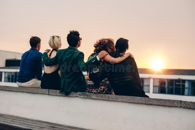 Friends relaxing on terrace in evening. Rear view of young men and women relaxing together on rooftop and looking at sunset. Multiracial friends sitting on stock image