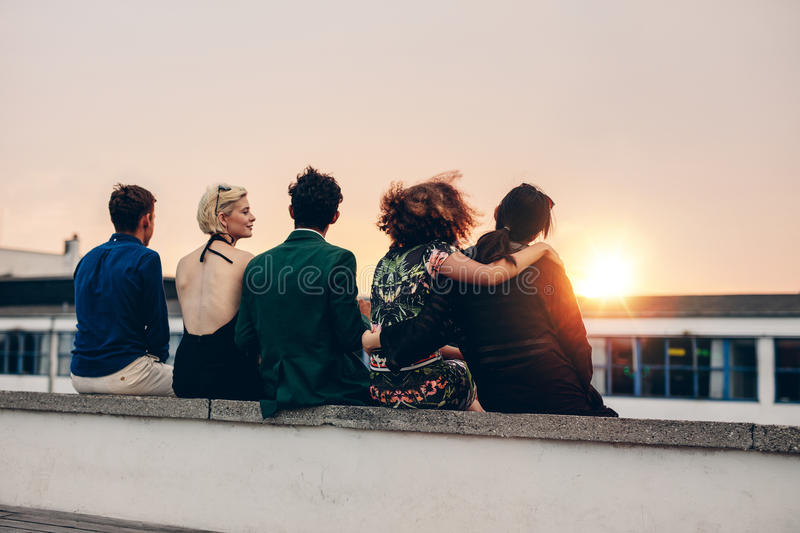 Friends relaxing on terrace in evening. Rear view of young friends relaxing together on rooftop at sunset. Young men and women sitting on terrace in evening royalty free stock image
