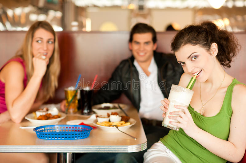 Friends in Restaurant eating fast food. Three friends in a restaurant or diner eating fries and drinking milkshakes, shot with available light, very selective royalty free stock images