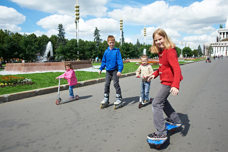 Friends riding a skateboard and scooter royalty free stock image
