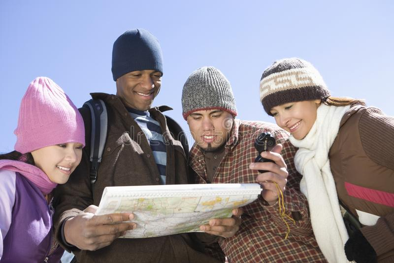 Friends With Roadmap Against Clear Sky. Four multiethnic friends looking at roadmap against clear blue sky stock image