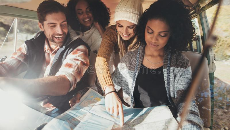 Friends on roadtrip reading map for directions royalty free stock photos