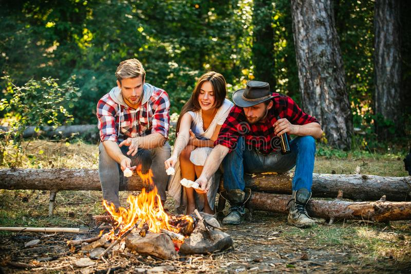 Friends roast marshmallow candies on the campfire in forest. Picnic friends. Tourism concept. Roasting marshmallows stock photo