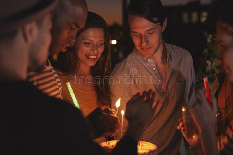 Friends on a rooftop lighting candles on a birthday cake stock photography