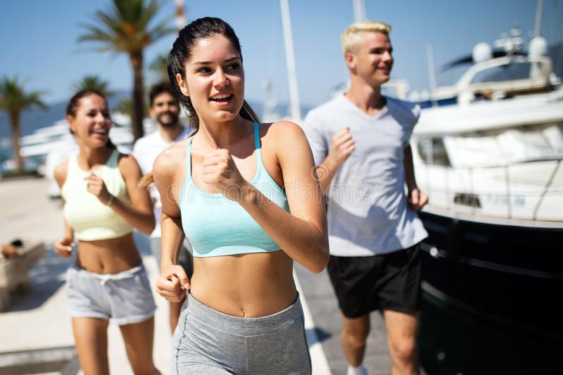 Friends running fitness training together outdoors living active healthy stock images