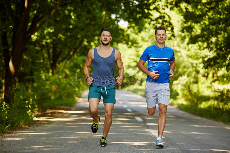 Friends running through forest royalty free stock images