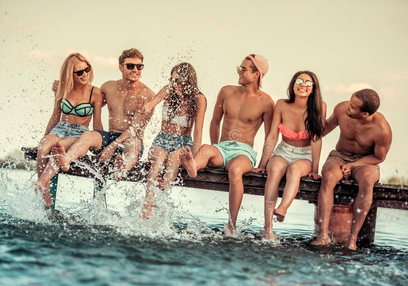Friends on the sea. Happy friends are splashing water and smiling while sitting on pier at the sea royalty free stock photo