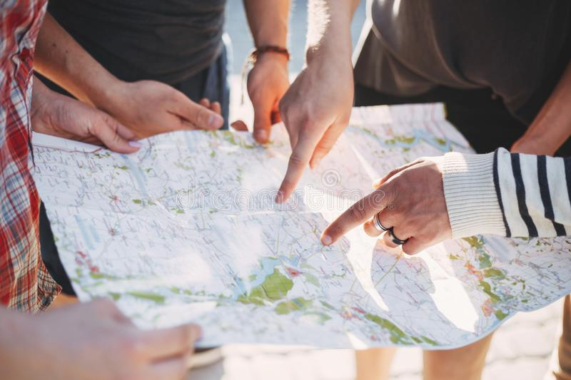 Friends searching location on map, planing journey stock photos