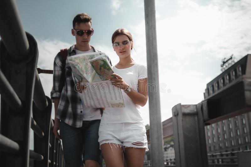 Friends Are Searching A Right Direction On The Map Outdoor. stock photo