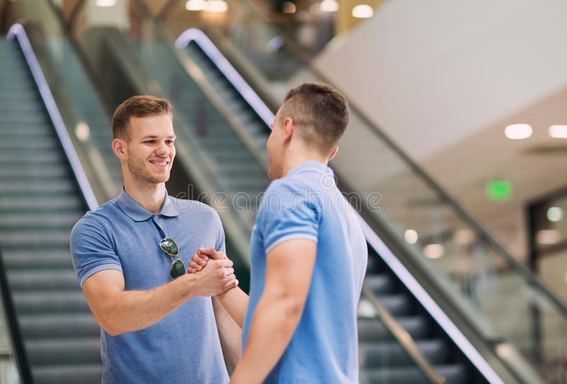 Friends shaking hands in a shopping mall royalty free stock photo