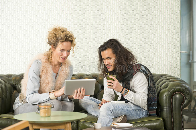 Friends sharing electronic information. Two friends sharing information and showing each other photos on an electroic tablet, sitting on a leather chesterfield stock photography
