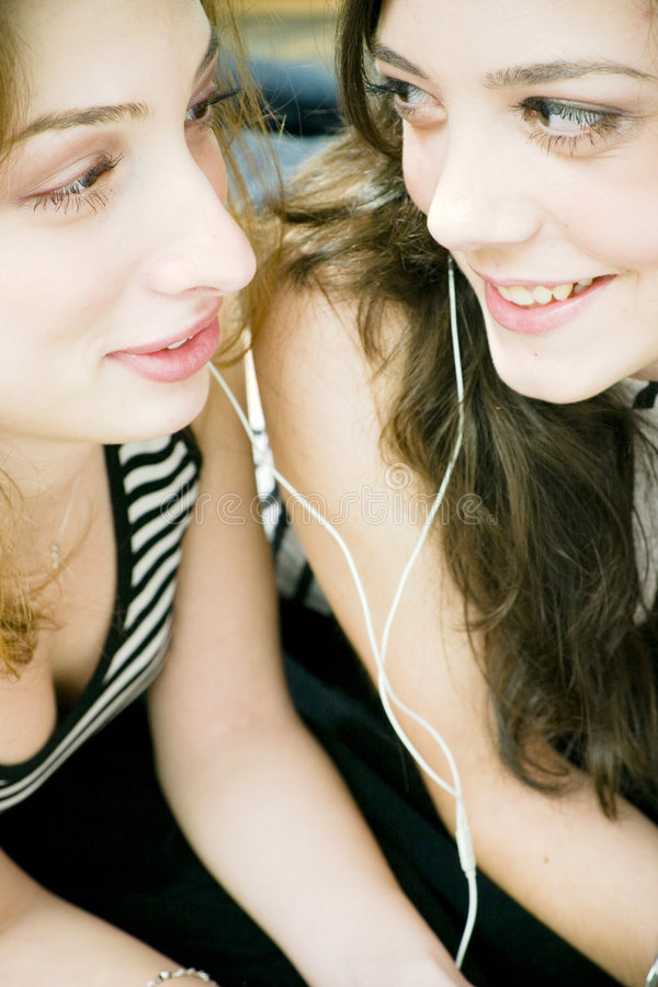 Friends sharing headphones royalty free stock photo