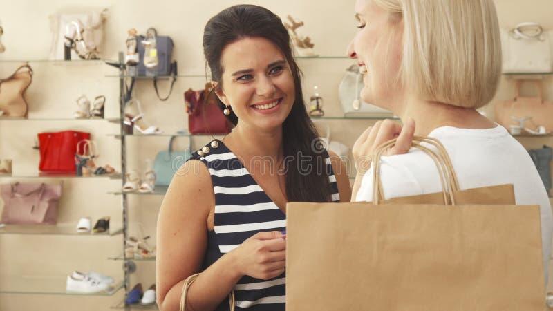Women talking in shoe shop stock photo