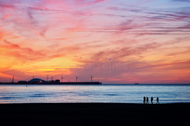 Friends silhouette walking on beach at sunset stock photo