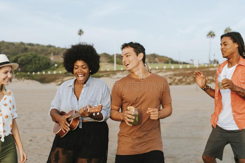 Friends singing and dancing at the beach royalty free stock photography