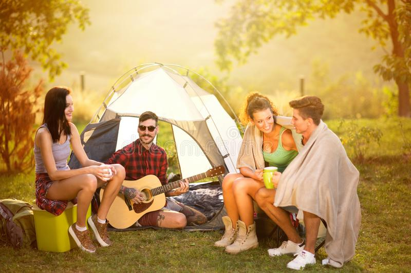 Friends singing and having fun camping together stock photos