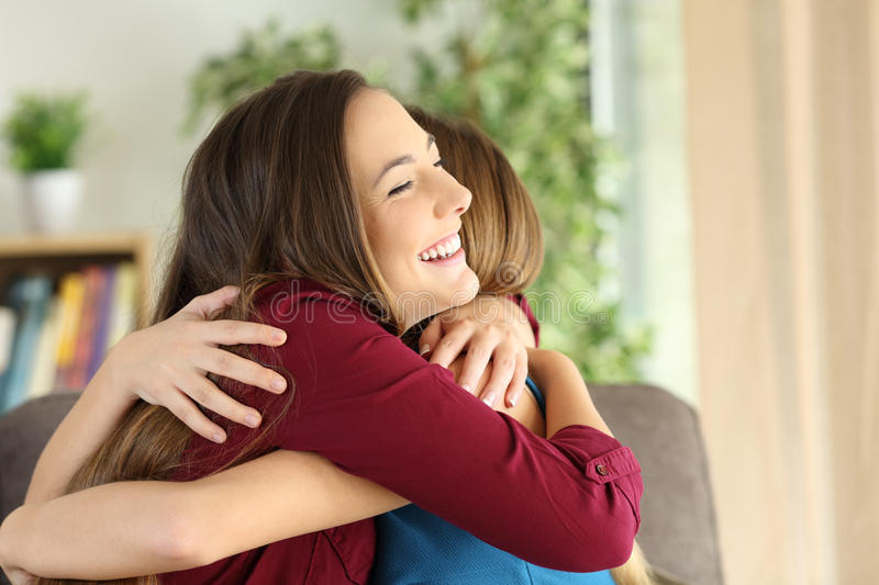 Friends or sisters embracing at home stock images