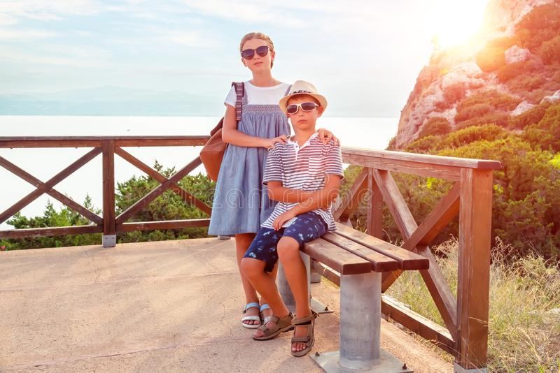 Friends sit on a bench against the backdrop of a beautiful sea landscape royalty free stock photo