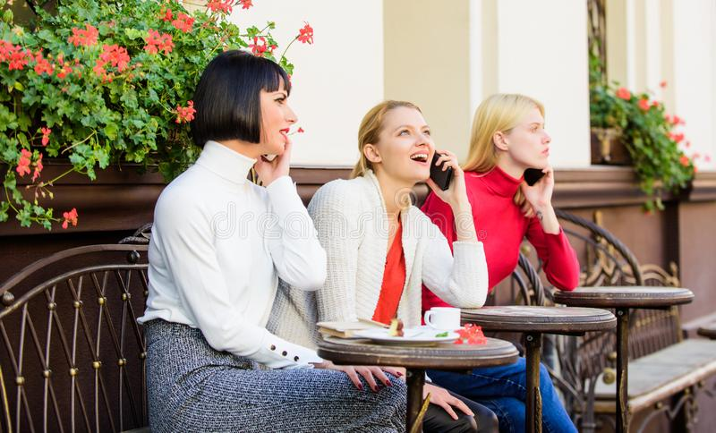 Friends sit in coffee shop and enjoy talk. Obsessed with speaking. Using digital devices. Group women cafe terrace stock photography