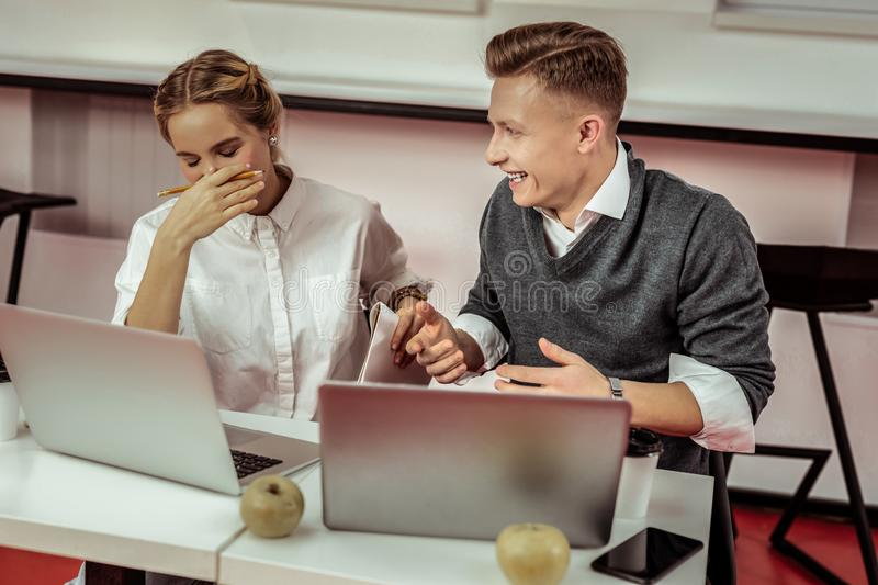 Active short-haired guy telling funny joke to his colleague royalty free stock image