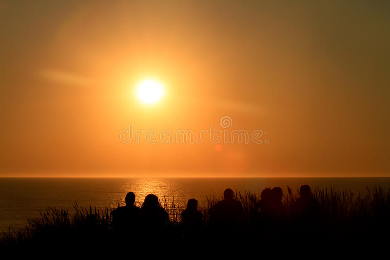 Friends sitting on dune in sunset stock image